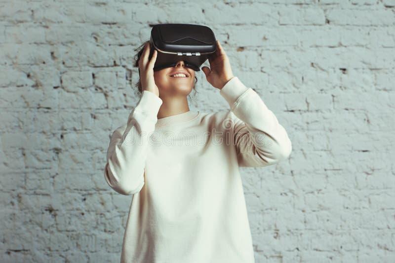 Przystojna młoda kobieta jest ubranym wirtualną słuchawki Uśmiechnięty modniś używa VR szkła Pusty pulower Biały cegły ściany tło fotografia royalty free