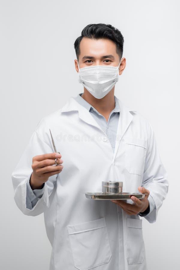 Przystojna młoda pielęgniarka w płaszczu medycznym trzyma nożyczki w narzędziach na tacce obraz royalty free