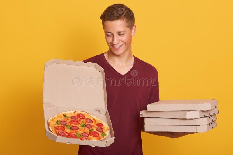 Przystojna młoda pracownica, ubrana w burgundy, zwykła koszulka z pizzą w pudełkach, patrząca na otwarte pudełko i uśmiechnięta, zdjęcia royalty free