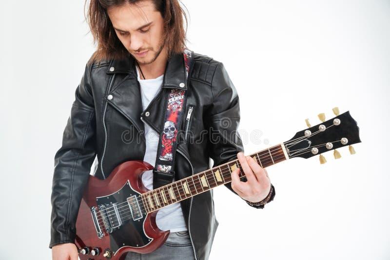 Przystojna młodego człowieka czerni skórzana kurtka bawić się gitarę elektryczną zdjęcia stock