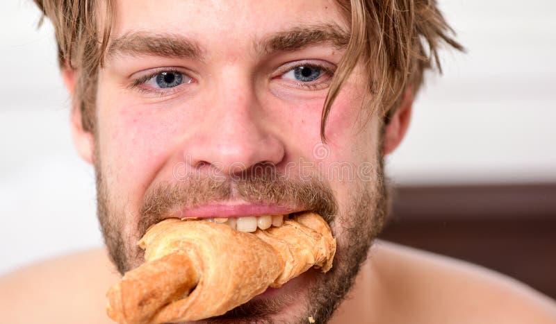Przystojna młodego człowieka napoju kawa i łasowania croissant w łóżku Młody szczęście mężczyzna na łóżku z cieszyć się wakacje i zdjęcie royalty free