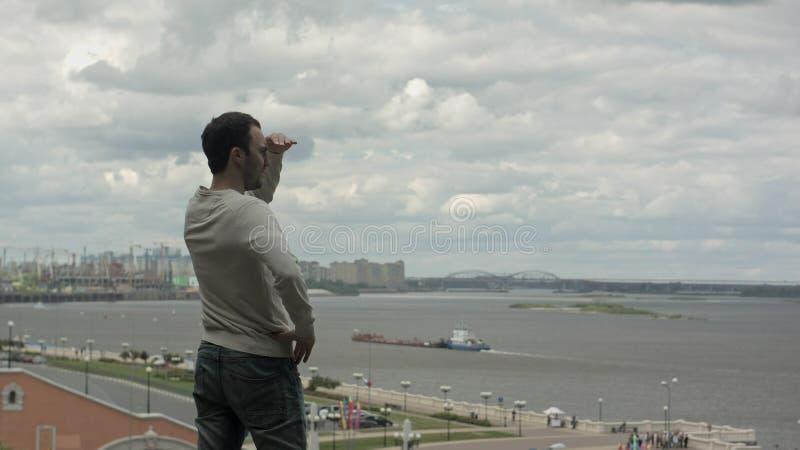 Przystojna młody człowiek pozycja blisko rzeki i patrzeć naprzód obraz stock