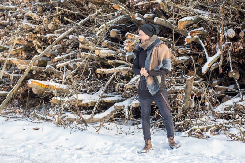 Przystojna młody człowiek pozycja przed rżniętym drewnem na śniegu obraz stock