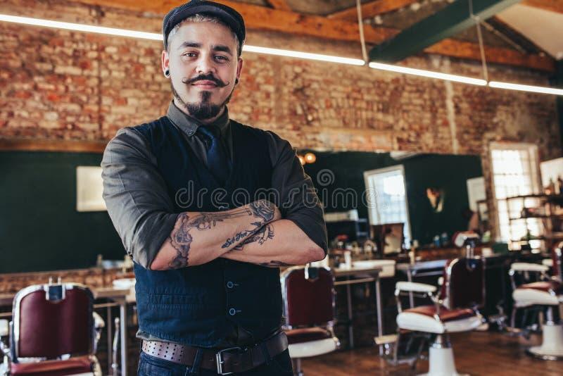 Przystojna młody człowiek pozycja przy fryzjera męskiego sklepem fotografia stock