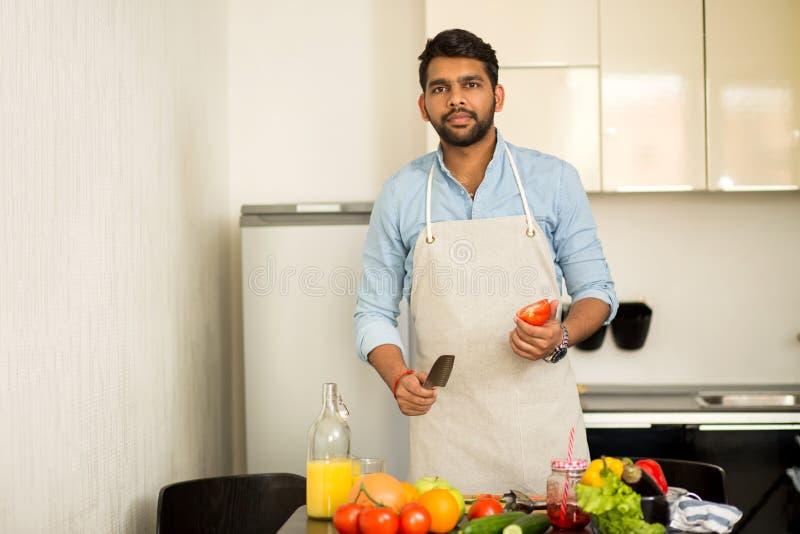 Przystojna młody człowiek pozycja w kuchni w domu obraz royalty free