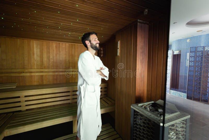 Przystojna młody człowiek pozycja w sauna ono uśmiecha się zdjęcie stock