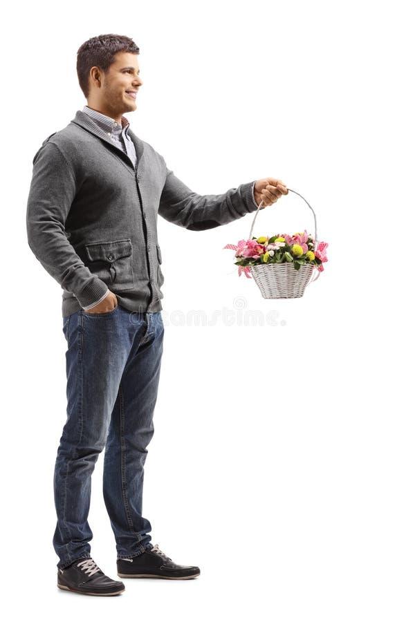 Przystojna młody człowiek pozycja z koszem pełno kwiaty zdjęcie royalty free