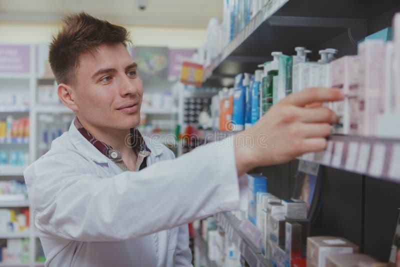 Przystojna m?ska farmaceuta pracuje przy jego aptek? obraz royalty free