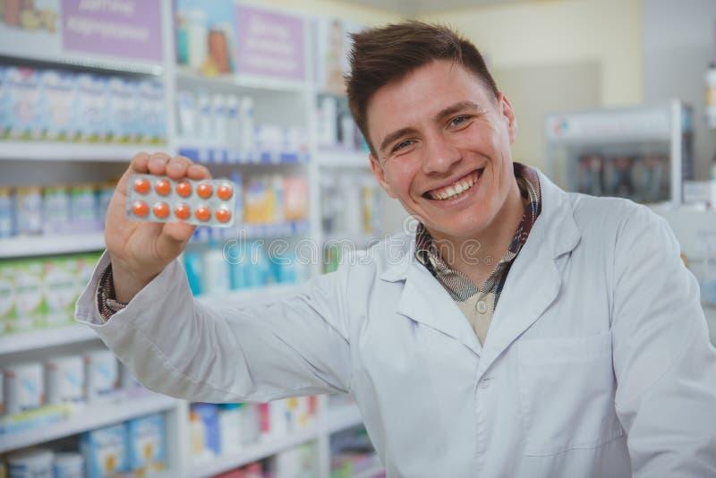 Przystojna m?ska farmaceuta pracuje przy jego aptek? zdjęcie stock