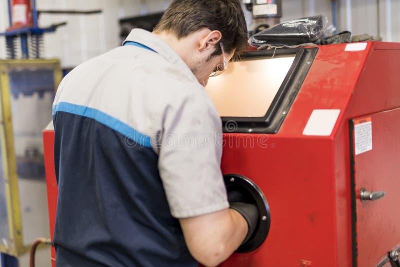 Przystojna mechanik praca w jednolitym działaniu na samochodowej części fotografia stock