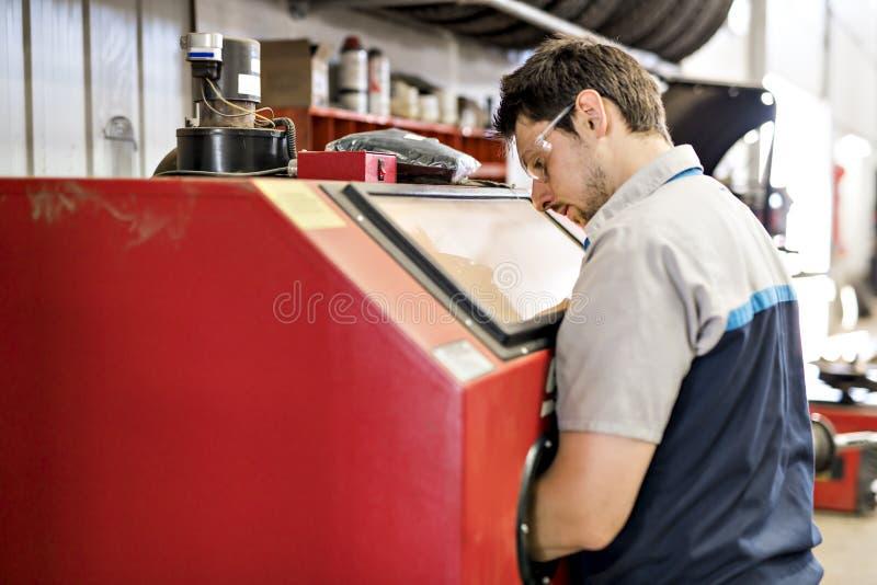 Przystojna mechanik praca w jednolitym działaniu na samochodowej części obrazy stock