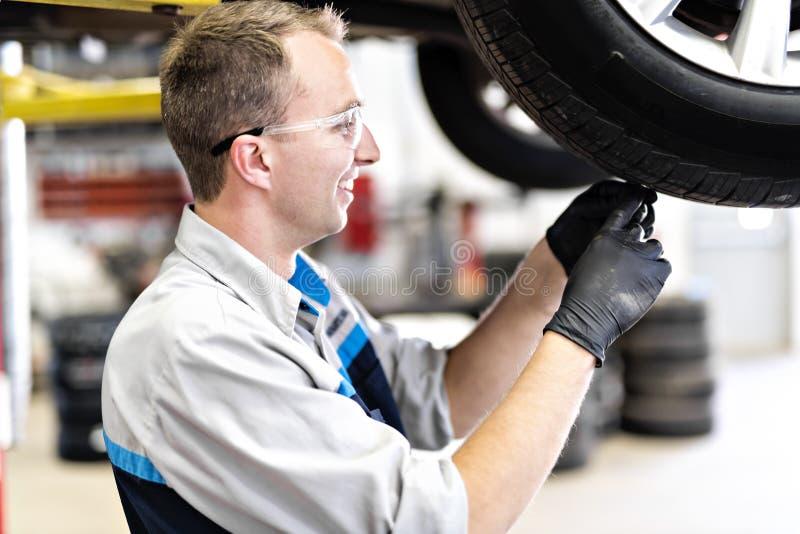 Przystojna mechanik praca w jednolitym działaniu na samochodowej czek opony odzieży obrazy royalty free