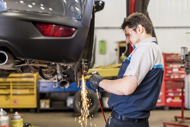 Przystojna mechanik praca w jednolitym działaniu na samochodowej robi iskrą zdjęcia royalty free