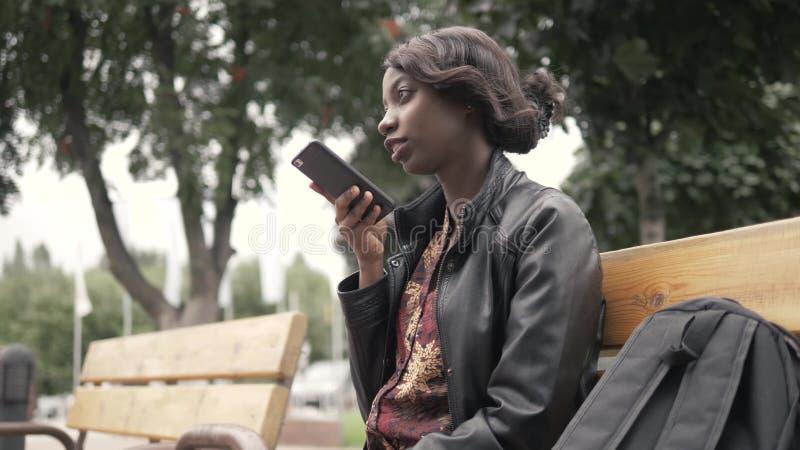 Przystojna modna amerykanin afrykańskiego pochodzenia murzynki nagrania głosu wiadomość na telefonie komórkowym plenerowym w mieś zdjęcia royalty free