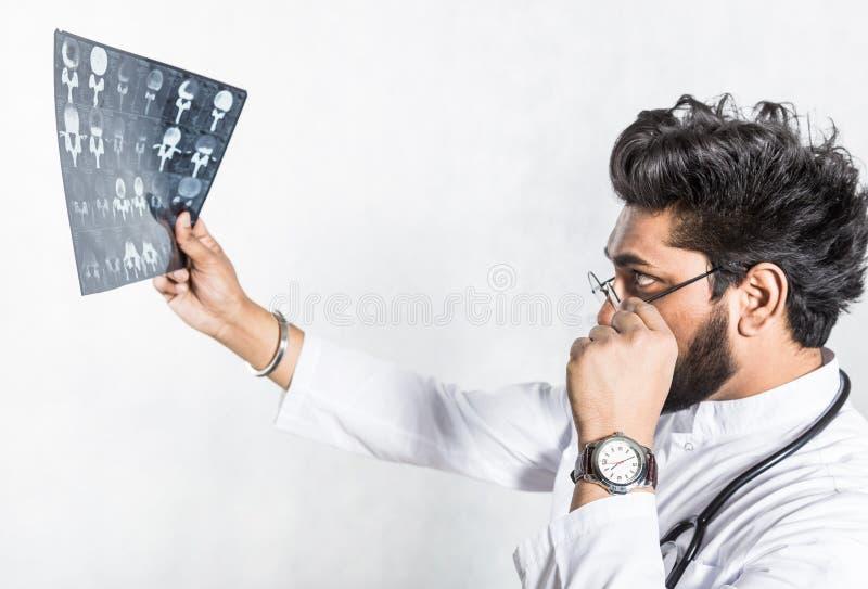 Przystojna potomstwo lekarka w bia?ym ?akiecie z stetoskopem attentively sprawdza pacjenta promieniowanie rentgenowskie obraz stock