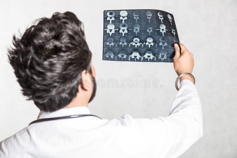 Przystojna potomstwo lekarka w bia?ym ?akiecie z stetoskopem attentively sprawdza pacjenta promieniowanie rentgenowskie fotografia stock