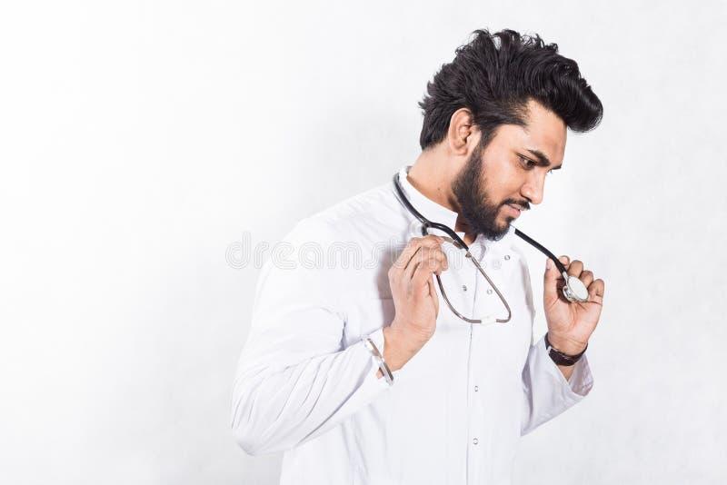 Przystojna potomstwo lekarka w bia?ym ?akiecie z stetoskopem t?o zamazywa? opieki poj?cia twarzy zdrowie maski pigu?k? ochronn? obraz stock