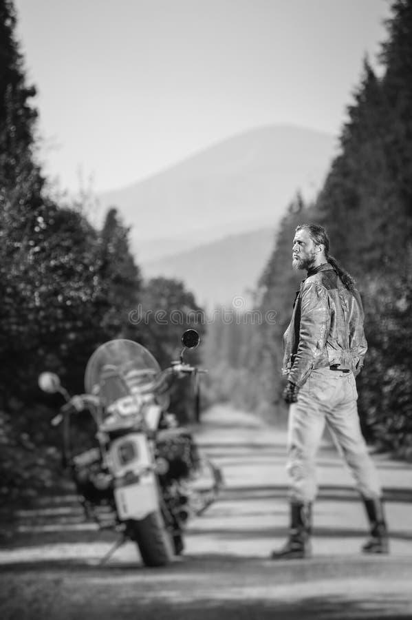 Przystojna rowerzysta pozycja jego na zamówienie krążownika motocyklem zdjęcia stock