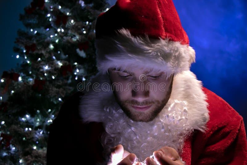 Przystojna samiec Santa patrzeje w dół przy światłami w jego rękach z choinką w tle z brodą zdjęcia royalty free