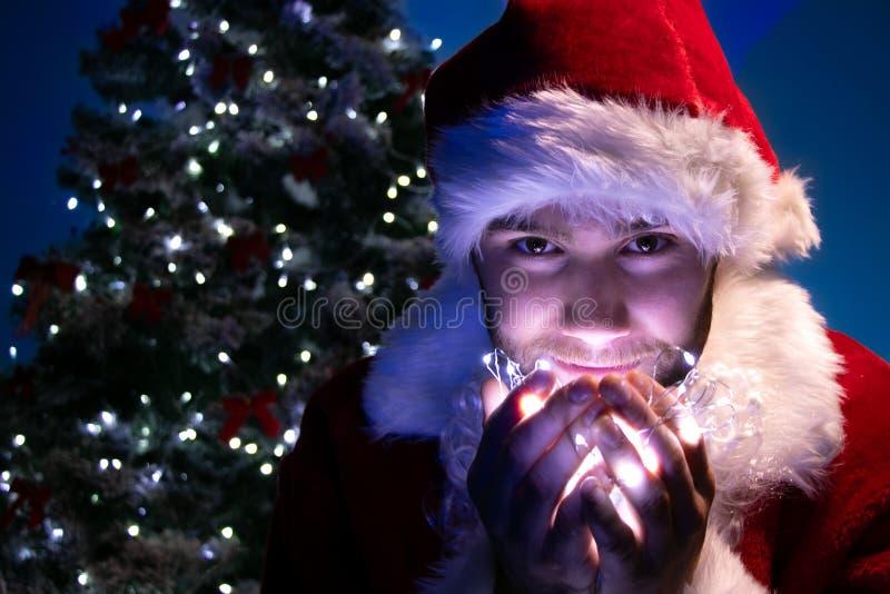 Przystojna samiec Santa uśmiecha się światła w jego ręce z choinką w tle i trzyma obraz stock