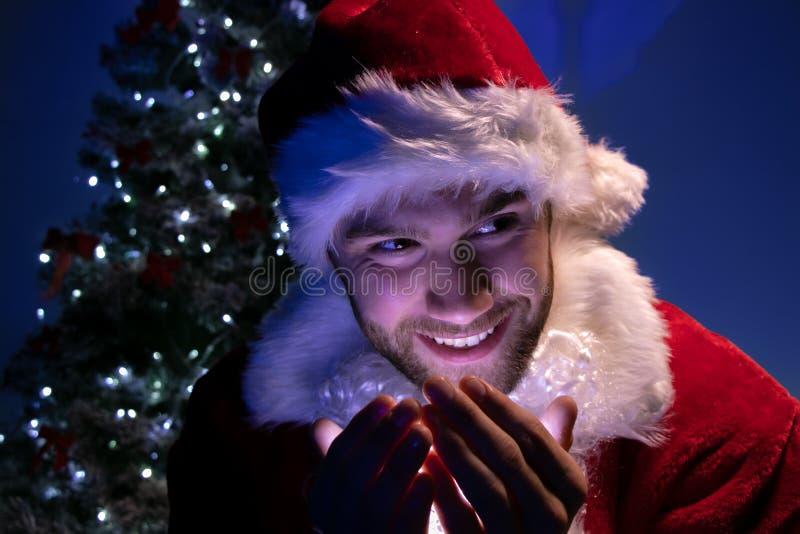 Przystojna samiec Santa uśmiecha się światła w jego ręce z choinką w tle i trzyma obrazy stock