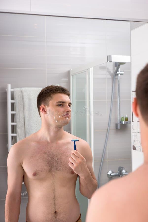 Przystojna samiec z cięciami na jego twarz po złego golenia mienia zdjęcie stock