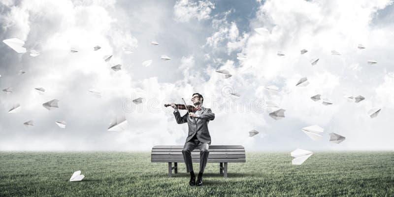 Przystojna skrzypaczka w parku na drewnianej ławki sztuce jego melodia obraz stock