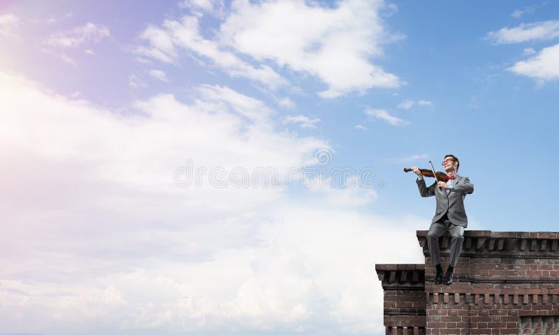 Przystojna skrzypaczka w szkłach na budynek krawędzi sztuce jego melodia zdjęcia royalty free