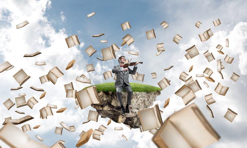 Przystojna skrzypaczki sztuka jego książki i melodia lata wokoło w niebie obraz stock