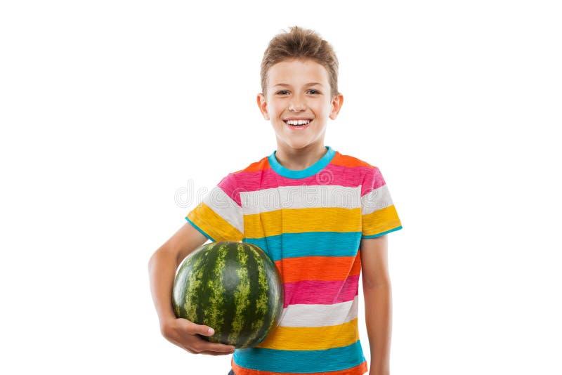 Przystojna uśmiechnięta dziecko chłopiec mienia zieleni arbuza owoc obraz stock