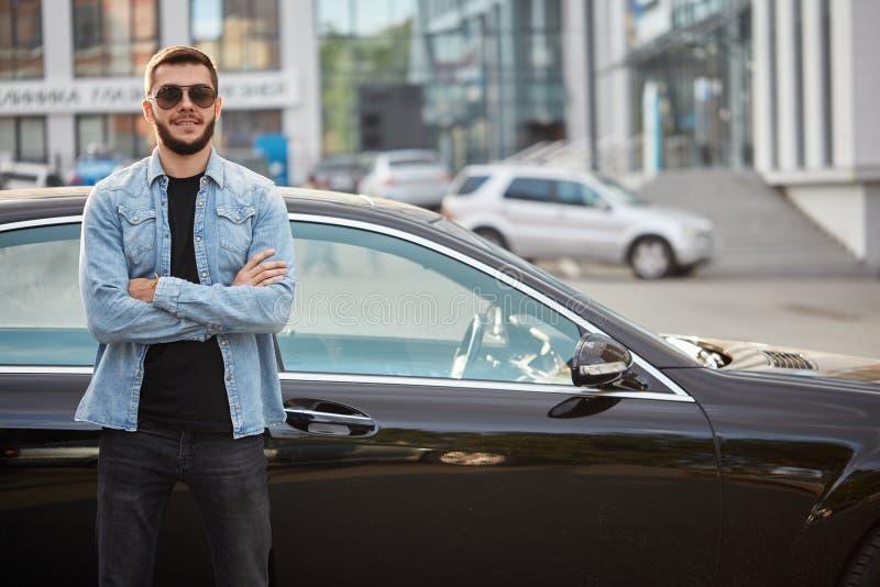 Przystojna uśmiechnięta mężczyzna pozycja przed samochodem zdjęcie stock