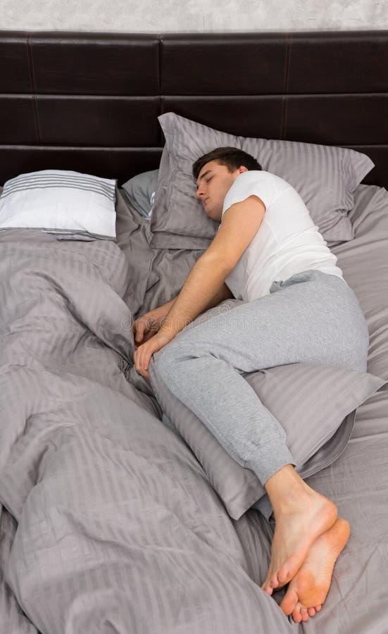 Przystojna zmęczona samiec śpi samotnie bez koc wewnątrz w piżamie zdjęcie royalty free