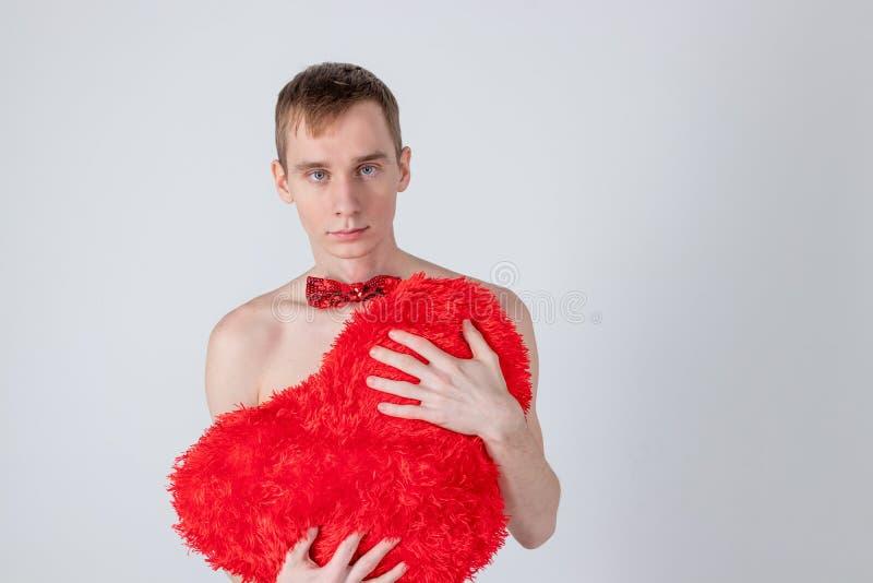 Przystojnego faceta chwyta duży czerwony serce na białym tle Miłość i romantyczny pojęcie Świętowanie walentynek dzień zdjęcie stock