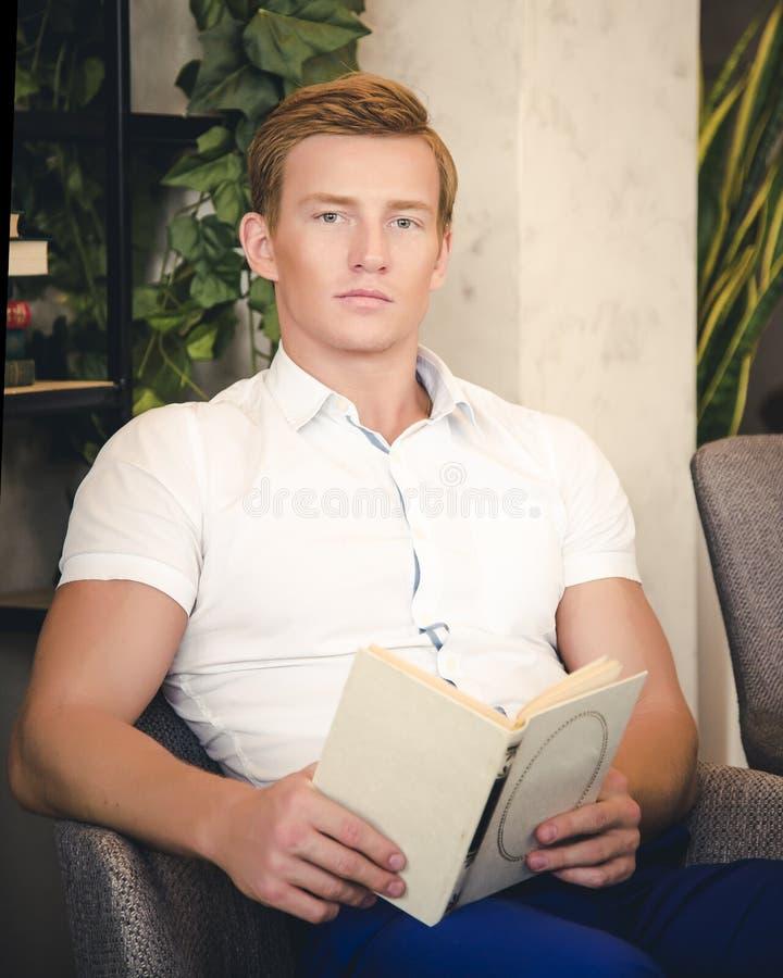 Przystojnego mężczyzna czytelnicza książka siedzi na leżance obrazy stock