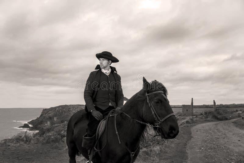 Przystojnego Męskiego konia jeźdza xviii wiek Poldark Regencyjny kostium z blaszanej kopalni ruinami i Atlantycki ocean w tle obrazy royalty free