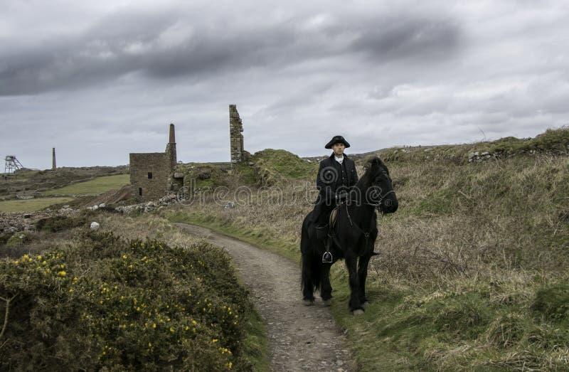 Przystojnego Męskiego konia jeźdza xviii wiek Poldark Regencyjny kostium z blaszanej kopalni ruinami i wieś w tle obraz stock