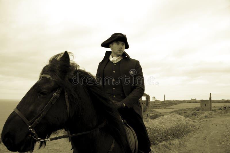 Przystojnego Męskiego konia jeźdza xviii wiek Poldark Regencyjny kostium z blaszanej kopalni ruinami i wieś w tle fotografia stock
