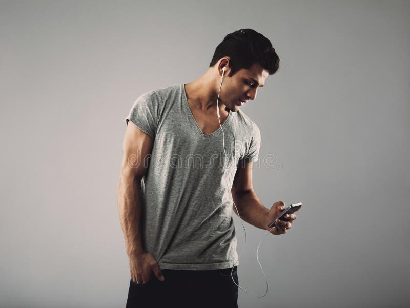 Przystojnego młodego człowieka słuchająca muzyka na telefonie komórkowym zdjęcia stock