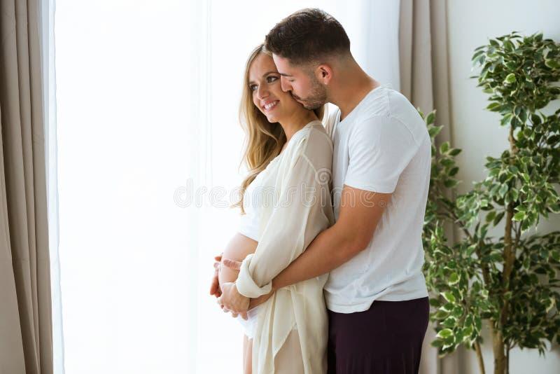 Przystojnego młodego człowieka wzruszający brzuch piękna kobieta w ciąży podczas gdy całujący w domu obrazy royalty free