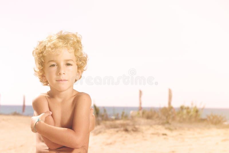przystojnego preteen chłopiec lokkin kamery ina pogodna plaża obraz royalty free