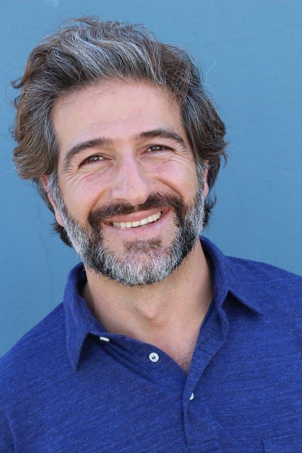 Przystojnego wieka średniego Śródziemnomorski mężczyzna w pracownianym portrecie na błękitny ścienny tła ono uśmiecha się zdjęcia stock
