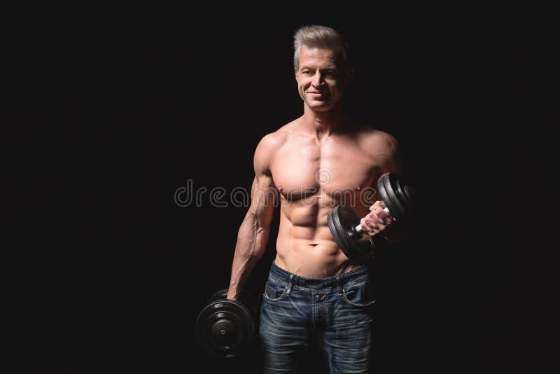 Przystojnej władzy sportowy mężczyzna pewnie patrzeje naprzód z dumbbell Silny bodybuilder z sześć paczkami, perfect abs zdjęcia stock
