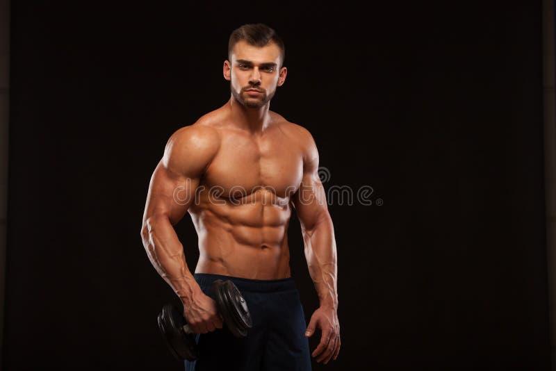 Przystojnej władzy sportowy mężczyzna z dumbbell pewnie patrzeje naprzód Silny bodybuilder z sześć paczkami, perfect abs zdjęcie royalty free