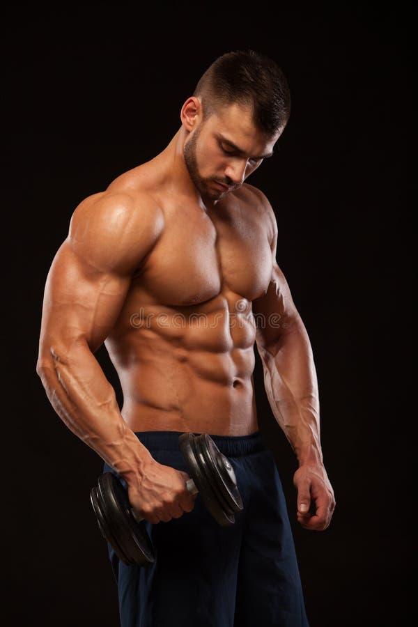 Przystojnej władzy sportowy mężczyzna z dumbbell pewnie patrzeje naprzód Silny bodybuilder z sześć paczkami, perfect abs zdjęcia stock