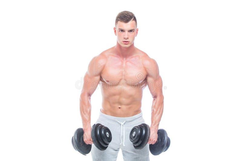 Przystojnej w?adzy sportowy m??czyzna pewnie patrzeje naprz?d z dumbbell Silny bodybuilder z sze?? paczkami, perfect abs obraz stock