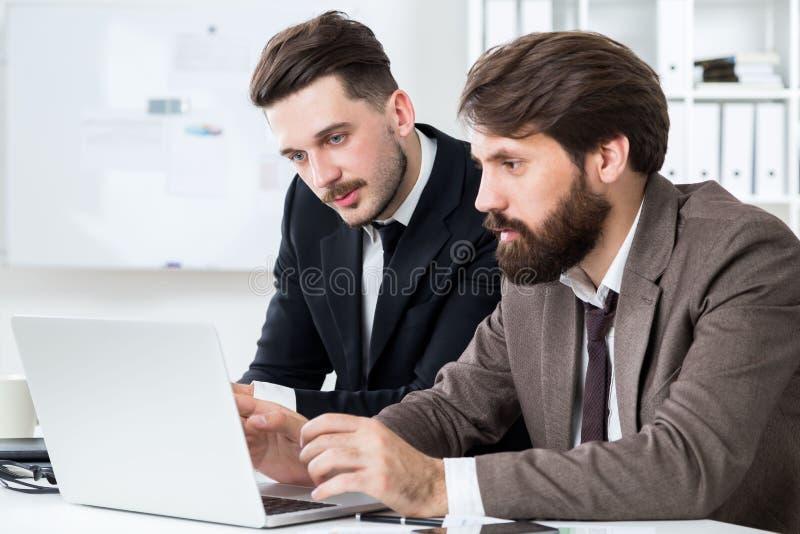 Przystojni biznesmeni dyskutuje projekt zdjęcie stock