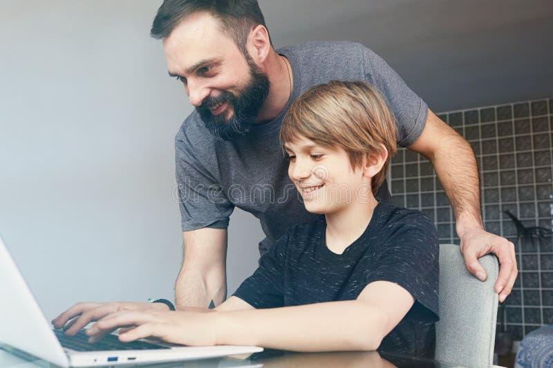 Przystojni brodaci potomstwa ojcują w przypadkowych ubraniach i jego ślicznym małym synu używa laptop w utrzymaniu podczas gdy pr fotografia stock