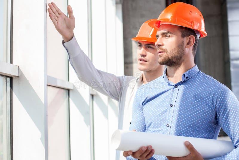 Przystojni budowniczowie dyskutują plan praca obrazy stock