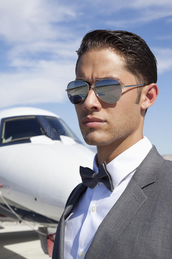 Przystojni młodzi człowiecy jest ubranym okulary przeciwsłonecznych z intymnym samolotem w tle obrazy royalty free