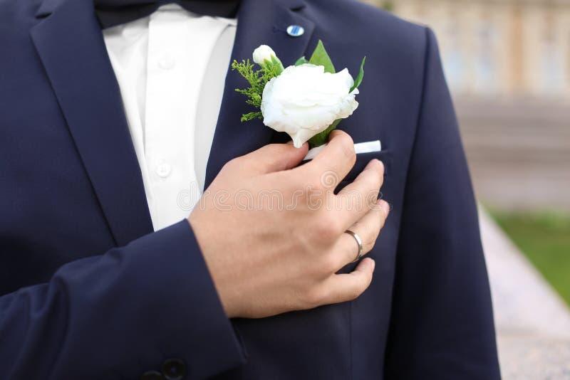 Przystojni potomstwa przygotowywają naprawiania buttonhole outdoors, zbliżenie fotografia royalty free
